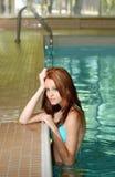 Reizvolle Brunettefrau, die auf Swimmingpoolrand sich lehnt Stockfoto