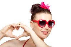 Reizvolle Brunettefrau in heart-shaped Gläsern Stockbild