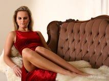 Reizvolle Dame, die das rote Kleid liegt auf einem Sofa trägt Stockfotografie