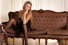 Reizvolle Dame, die erotische Wäsche auf einem Sofa trägt Lizenzfreies Stockbild
