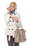 Reizvolle Dame, die mit Mobiltelefon im Studio aufwirft Lizenzfreies Stockfoto