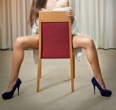 Reizvolle Fahrwerkbeine in den schwarzen hohen Absätzen auf Stuhl im Hotel Lizenzfreie Stockfotos