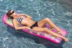 Reizvolle Frau auf bunter Poolhin- und herbewegung Lizenzfreies Stockfoto