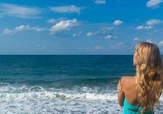 Reizvolle Frau auf einem Strand, der weit auf Horizont schaut Stockbilder
