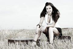Reizvolle Frau auf Koffer in der Landschaft Lizenzfreies Stockfoto