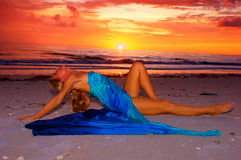 Reizvolle Frau auf Strand am Sonnenuntergang Stockfotografie