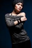Reizvolle Frau, die über dunklem Hintergrund aufwirft Lizenzfreies Stockbild