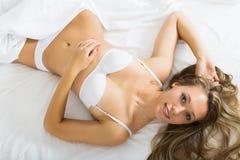 Reizvolle Frau, die auf Bett legt Lizenzfreies Stockfoto