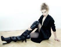 Reizvolle Frau, die auf dem Fußboden sitzt Stockfoto