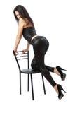 Reizvolle Frau, die auf dem Stuhl sich lehnt Stockfotos