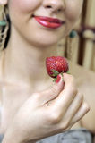 Reizvolle Frau, die eine Erdbeere schmeckt Lizenzfreie Stockfotografie