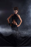 Reizvolle Frau, die in einem schwarzen Kleid aufwirft Lizenzfreies Stockfoto