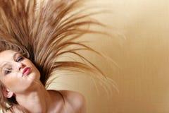 Reizvolle Frau, die Haar leicht schlägt Stockbild