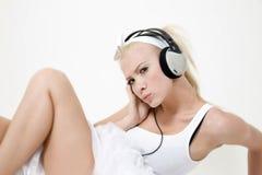 Reizvolle Frau, die Musik mit Kopfhörern hört Lizenzfreie Stockfotografie