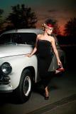 Reizvolle Frau, die nahes Auto in der Retro- Art steht Stockbild