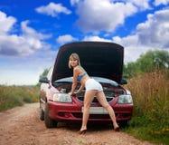 Reizvolle Frau, die versucht, Auto zu reparieren Lizenzfreie Stockfotografie
