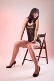 Reizvolle Frau gesetzt auf hölzernem Stuhl Lizenzfreie Stockbilder