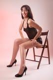 Reizvolle Frau gesetzt auf hölzernem Stuhl Lizenzfreie Stockfotografie