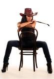 Reizvolle Frau im Cowboyhut sitzt auf Stuhl Stockfoto