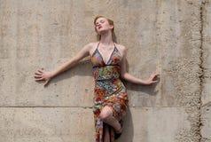 Reizvolle Frau im Kleid, das an der Wand sich lehnt Lizenzfreies Stockbild