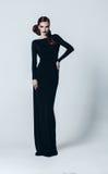 Reizvolle Frau im langen schwarzen Kleid Stockfotos