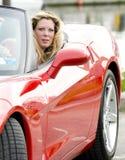 Reizvolle Frau im roten Sportauto Stockfoto