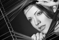 Reizvolle Frau im schwarzen Kleid und im Jalousie stockbilder