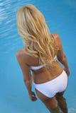 Reizvolle Frau im weißen Bikini betritt Swimmingpool Lizenzfreie Stockfotografie