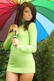 Reizvolle Frau mit buntem Regenschirm stockbild