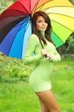 Reizvolle Frau mit buntem Regenschirm stockfoto