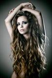 Reizvolle Frau mit dem langen lockigen Haar stockbild