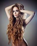 Reizvolle Frau mit dem langen lockigen Haar lizenzfreie stockfotografie