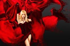 Reizvolle Frau mit dem Spritzen der roten Seide Lizenzfreies Stockfoto
