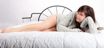 Reizvolle Frau mit den langen Fahrwerkbeinen auf Bett Stockbild