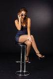 Reizvolle Frau mit den Sonnenbrillen, die auf einem Stuhl sitzen Lizenzfreie Stockbilder