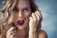 Reizvolle Frau mit einer Halskette in ihrem Mund Stockbilder