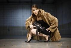 Reizvolle Frau mit Gewehr Stockfotografie