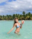 Reizvolle Frau mit großem Seashell auf karibischem Strand Lizenzfreie Stockfotografie