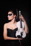 Reizvolle Frau mit schwarzer Partyschablone und weißer Violine Stockfotografie