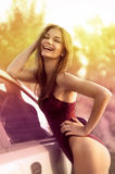 Reizvolle Frau und Auto auf grünem Feld Lizenzfreies Stockbild