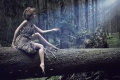 Reizvolle Frauen, die auf dem Baum sitzen Lizenzfreies Stockfoto