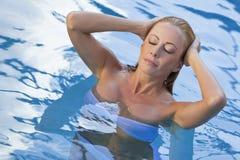 Reizvolle Frauen-tragender weißer Bikini im Swimmingpool Lizenzfreie Stockfotografie
