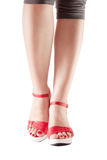 Reizvolle Frauenfahrwerkbeine in den roten Schuhen Stockfoto