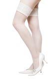 Reizvolle Frauenfahrwerkbeine in den weißen Strümpfen stockbild