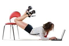 Reizvolle Geschäftsfrau, die auf Stuhl mit Laptop liegt stockbilder