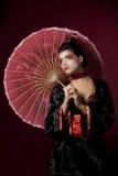Reizvolle japanische Geisha, die seitlich schaut Stockbild