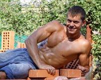 Reizvolle junge Arbeitskraft des Muskels, die auf Ziegelsteinen liegt Stockbilder