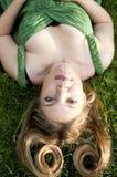 Reizvolle junge blonde Frau, die auf grünes Gras legt Lizenzfreies Stockfoto