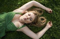 Reizvolle junge blonde Frau, die auf grünes Gras legt Lizenzfreies Stockbild