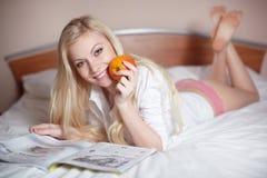 Reizvolle junge blonde Frau, die in Bett legt Stockbilder